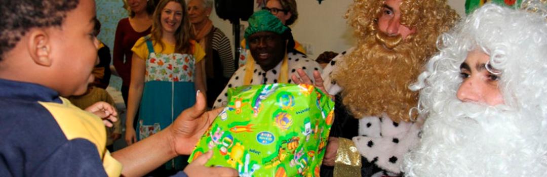 niño recibiendo regalo de un rey mago en fiesta de reyes por la integración social