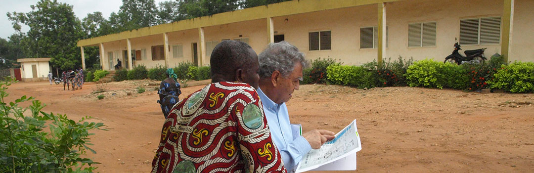Dos hombres mirando documentos de proyecto de salud infantil con hospital de Dongba de fondo