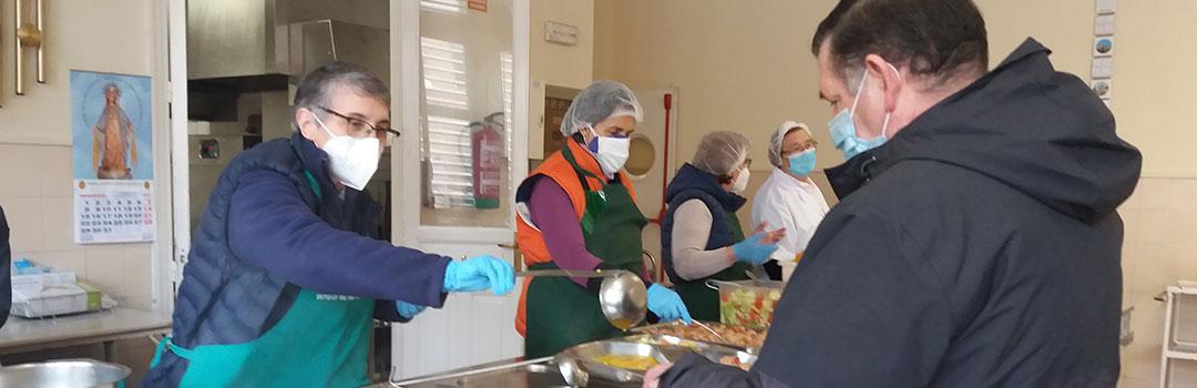 voluntarios dando de comer a personas en comedor social en Madrid