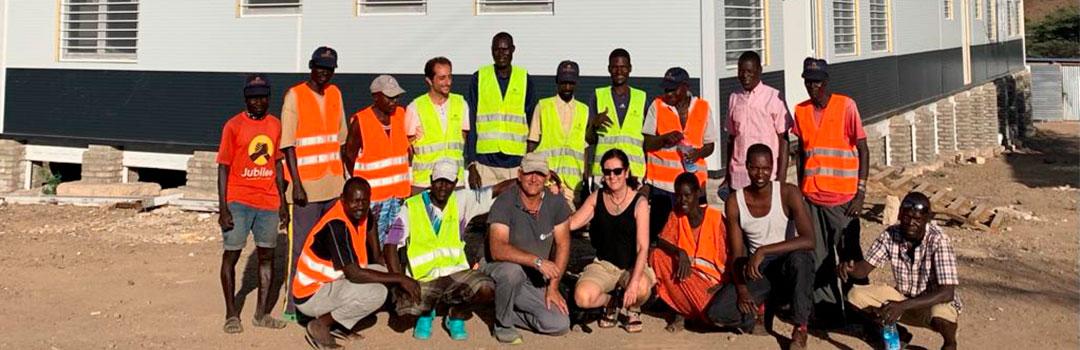 Personal médico y de construcción con el hopsital de Turkana de fondo. Derecho a la salud